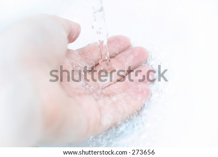 Focus on hand center, water is in motion. - stock photo