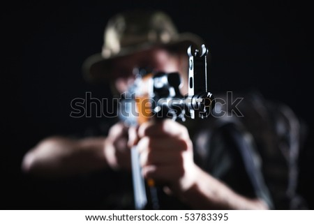 Focus on Kalashnikov rifle being held by blurred soldier in combat.