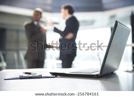 Focus on laptop on the table. Blurred people on background. - stock photo