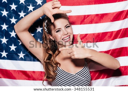 Focus on me! Cheerful young woman making finger frame and looking through it with smile while standing against American national flag