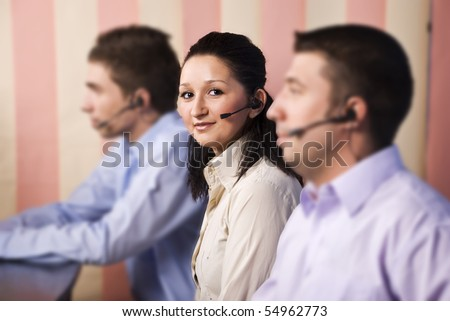 Focus on nice young woman customer service representative looking and smiling at you in the middle of two men team in office,vertical blinds background - stock photo