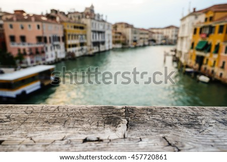 Focus on old wooden platform, water, canal,bridge and traditional buildings as background, Venice,Italy, Europe. - stock photo
