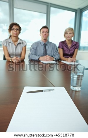 Focus on paper and pen on table. In the background panel of business people sitting conducting job interview. - stock photo