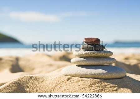Focus on pile of pebbles on the sand with ocean in the background. - stock photo