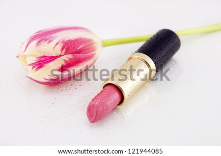 Focus on pink lipstick with a pink tulip in the background. - stock photo