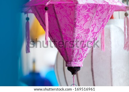 Focus on pink vietnamese lantern among others on market. Most popular national souvenir in Vietnam. Usually made of bamboo and silk. Symbols and traditions of country. Travelling and tourism. - stock photo