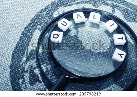 Focus on quality concept with magnifying glass - stock photo