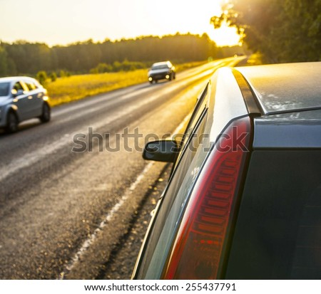 Focus on red headlight Stop car on the nature near asphalt highway road against evening sunset sky Sun rays shine through green trees summer forest Non urban scene - stock photo