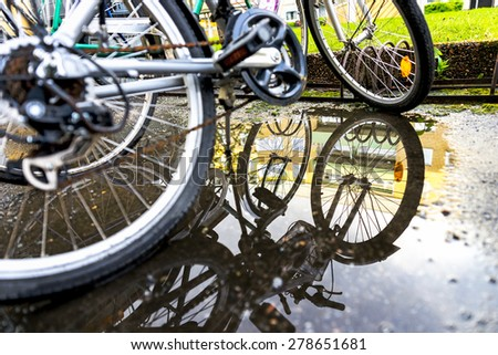 Focus on reflection in puddle with rain water of bikes parked by bicycle rack  - stock photo