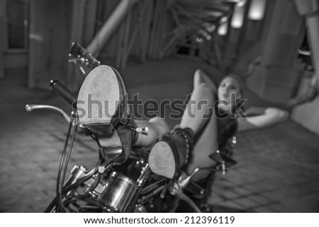 Focus on shoes Sexy girl lies on a motorcycle arch in dark room Dreaming fashion woman with long slim sexy legs wearing leather jacket and short jeans shorts White and black