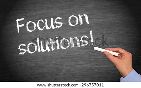 Focus on solutions ! - Woman writing text on chalkboard - Business and Teamwork concept - stock photo