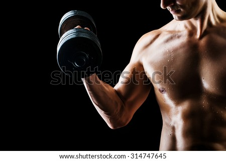 Focus on stomach. Dark contrast shot of young muscular fitness man stomach and arm. Bodybuilder with beads of sweat training in gym. Working out with dumbbells on black background - stock photo
