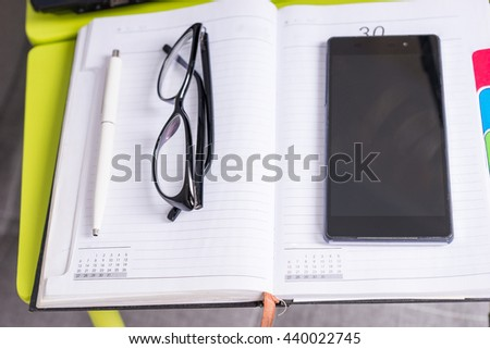 Focus on stylish glasses lying on the laptop table near open blank page of a diary with a pen for making appointments, organising a schedule and mobile phone - stock photo