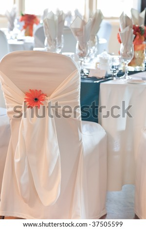 Focus on the back of a wedding chair and chair cover with ornamental orange daisy, and tables and bright window with natural daylight in the background.
