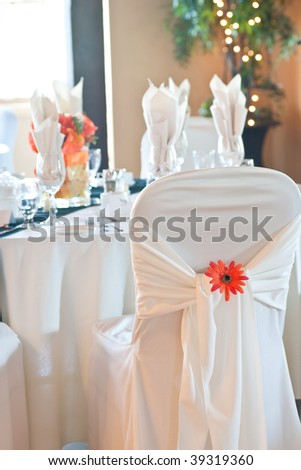 Focus on the back of a wedding chair and chair cover with ornamental orange daisy, and tables and bright window with natural daylight in the background. - stock photo