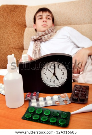Focus on the Clock. Sick Teenager on the Bed at the Home - stock photo