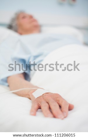 Focus on the hand of a patient in hospital ward - stock photo