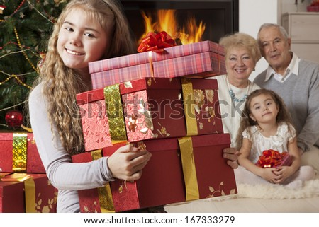 Focus on the happy little girl showing at the camera Christmas presents   - stock photo