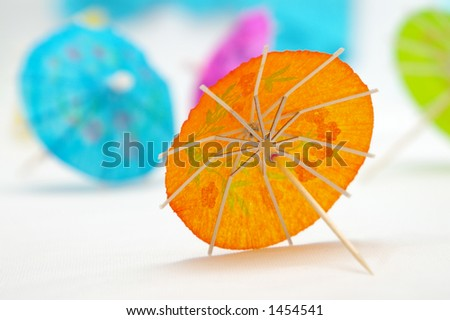 Focus on the inside of an orange cocktail umbrella, with other colorful umbrellas in the background. - stock photo