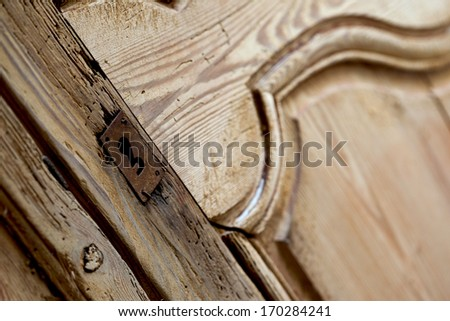 Focus on the lock of an old wooden cabinet - stock photo