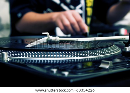 Focus on the professional turntable with a DJ adjusting the volume on controller - stock photo