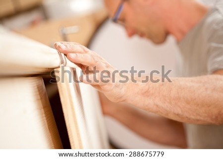 focus on the robust hand of a carpenter placing a flap (a wooden board) on a piece of a handcrafted wooden piece of furniture - stock photo