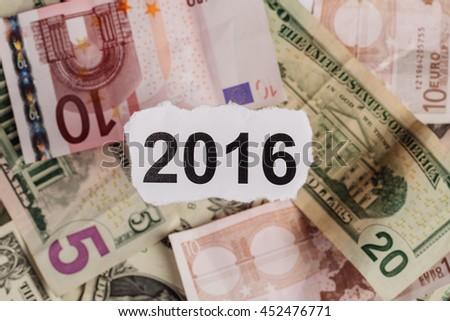 Focus on the words 2016 on piece of torn white paper with USDdollars and EURO currency as a background. Concepts of investment and business. - stock photo