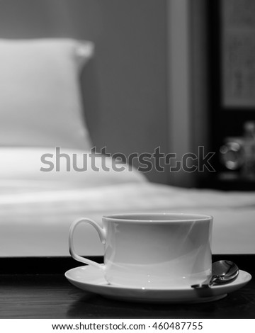 Focus on white cup of coffee, bed and pillow as background. hotel room or bedroom concept.