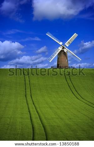 Focus on windmill in a beautiful field landscape - stock photo
