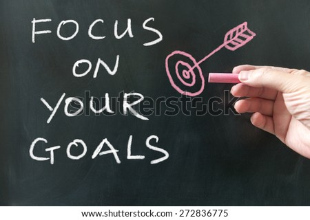 Focus on your goals words written on the blackboard using chalk - stock photo