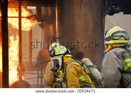 Focus sits on the firefighter in the middle between the two others. - stock photo