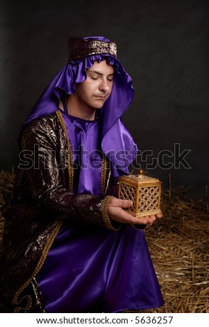 Focus to gift.  Wise man kneeling on straw in a stable, bringing a gift for the baby Jesus. - stock photo
