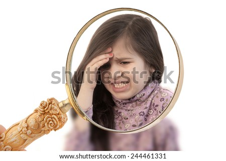 Focus with a magnifying glass on a  little girl with her hand held to her forehead with painful expression showing headache - stock photo