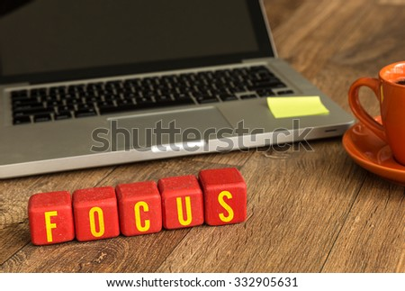 Focus written on a wooden cube in front of a laptop - stock photo