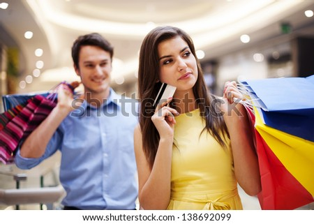 Focus young woman holding credit card and shopping bags - stock photo