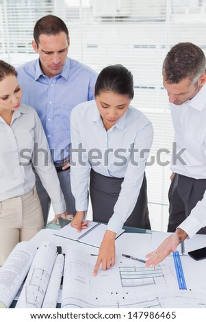 Focused architects interacting and analyzing plans together in bright office - stock photo