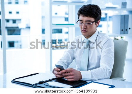 Focused asian businessman using his phone in his office