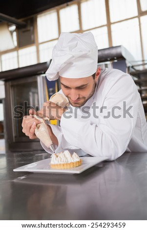 Focused baker preparing handmade cake in the kitchen of the bakery - stock photo