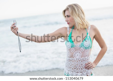 Focused blonde woman in white beach dress taking a picture of herself on the beach