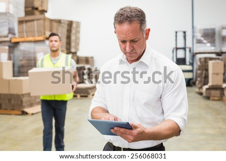 Focused boss using digital tablet in warehouse