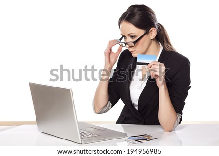 focused business woman holding credit card and looking at her laptop - stock photo