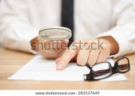 Focused businessman is reading through  magnifying glass document - stock photo