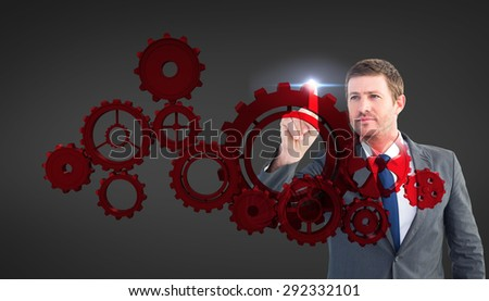 Focused businessman pointing with finger against grey vignette - stock photo