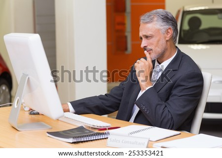Focused businessman using his laptop at new car showroom - stock photo
