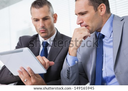 Focused businessmen analyzing documents on their tablet in bright office - stock photo