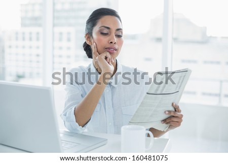 Focused businesswoman reading newspaper sitting at her desk in bright office