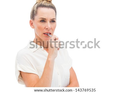 Focused businesswoman with pen on mouth looking at the camera
