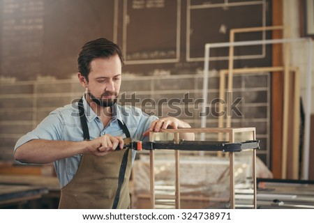 Focused capenter carefully making a wood and glass display case in his workshop with the skill of his trade - stock photo