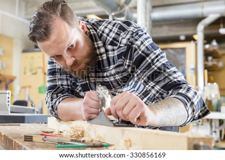 Focused carpenter work with plane on wood plank in workshop - stock photo