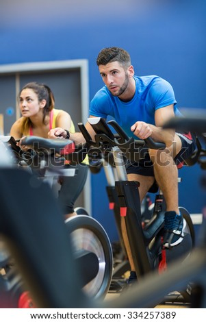 Focused couple using exercise bikes at the gym - stock photo